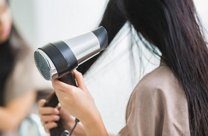сушит волосы феном