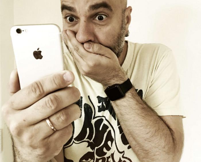 мужчина смотрит с ужасом в смартфон