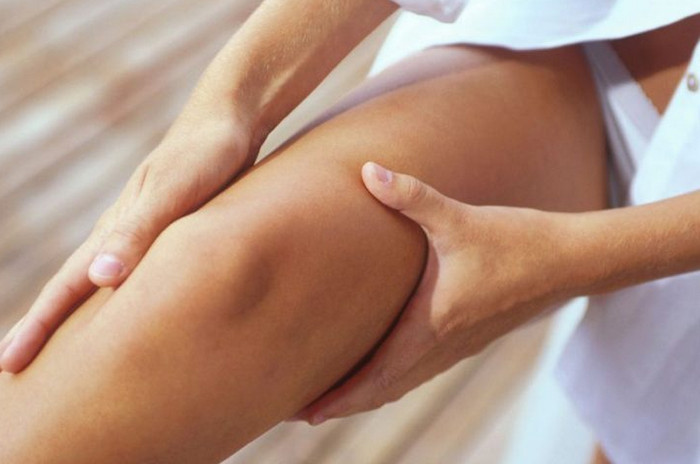 массирует колено
