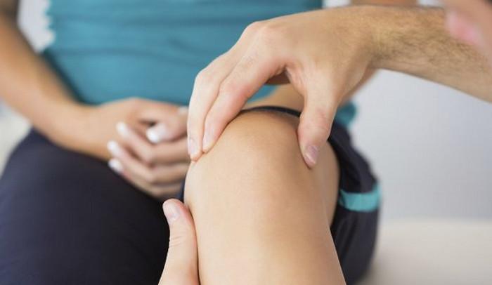 врач трогает колено