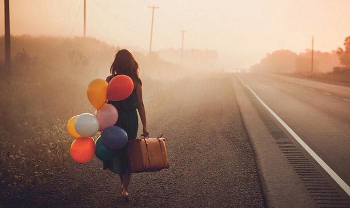 девушка с шариками идет по дороге