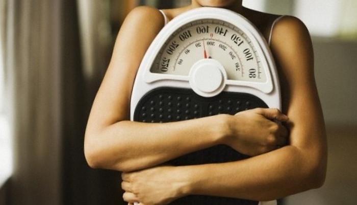 держит в руках весы
