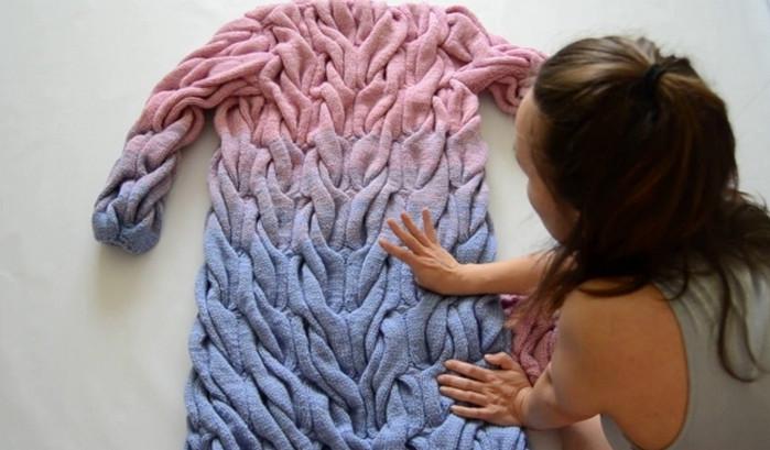 раскладывает свитер горизонтально