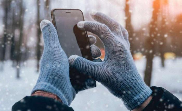 пользуется телефоном на морозе