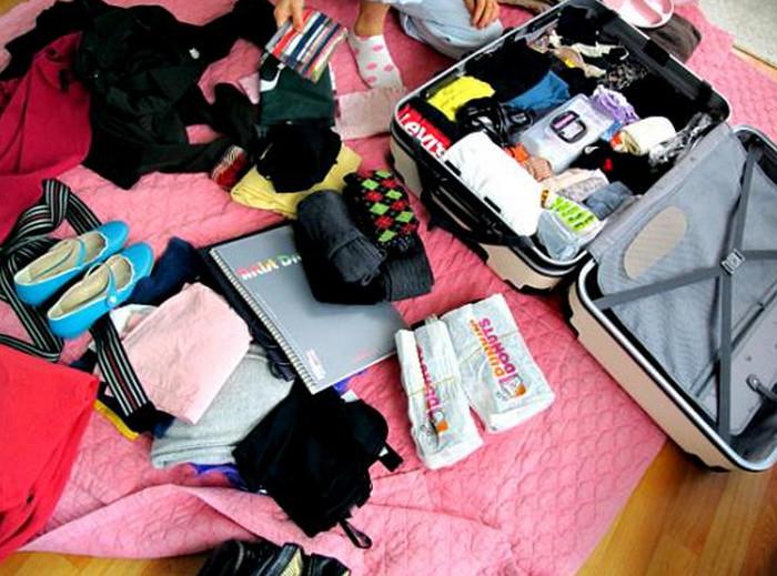 много вещей возле чемодана